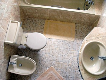 Fully tiled bathroom with bath tub and separate shower cubicle.